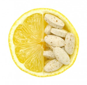 Close up of lemon and pills isolated – vitamin concept
