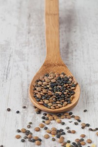 Bunch of raw lentils on a wooden spoon